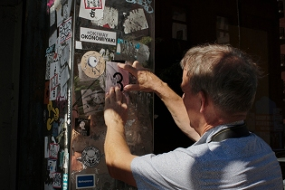 στερεώνοντας με κολλητική ταινία μια φωτογραφία επάνω σε μια κολόνα