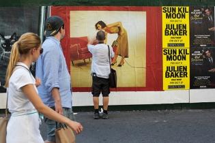 στερεώνοντας με κολλητική ταινία μια φωτογραφία επάνω σε μια υπαίθρια διαφήμιση